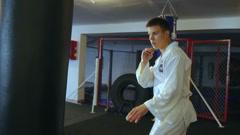 Taekwondo training by handsome sportsman, backlit. Slowly - stock footage