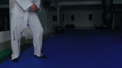 Man in white uniform training legs with punching bag in the gym. Slowly Stock Footage
