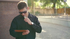 Happy businessman using tablet and smoking e-cigarette outdoor. Slowly - stock footage