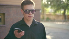 Young businessman speaking on the phone and smoking e-cigarette on street - stock footage