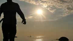 Closeup Silhouette of man with Kalashnikov in waters against sunset Stock Footage