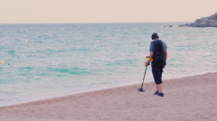 Lloret de Mar, Spain - Man with metal detector looking for coins Stock Footage