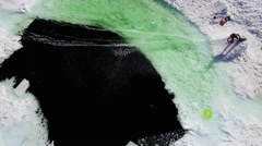 Snowboarder Rides Across Frozen Green and Blue Snow Ice Water Slush Cup Pond Stock Footage