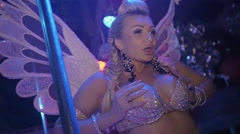 Go go girl with wings, in glow bra compress the breast in nightclub. Slow motion Stock Footage