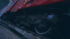 Close-up of wheels and other equipment under the carriage of the red fast train Stock Footage