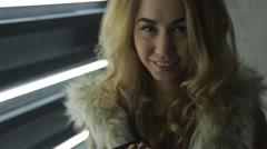 Attractive blonde woman dressed in fur jacket flirts Stock Footage