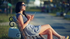 Beautiful woman sitting on the outdoor bench and typing on the phone Stock Footage