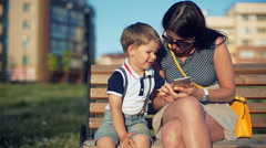 Mother and her small son are laughing and watching something on smart phone in Stock Footage