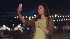 Beautiful girl doing selfie by phone at the fair night Stock Footage