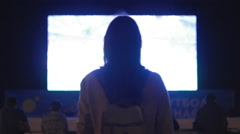 Beautiful girl looking video on the big screen at night - stock footage