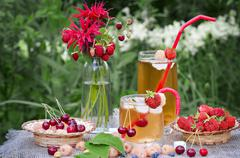 Cold tea with bergamot and berries Stock Photos