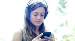 Pretty young girl listening music in headphones and make a selfie Stock Footage