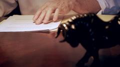 Businessman working on paperwork rack focus to bull 4k Stock Footage