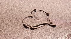 Woman Hand Paint Heart on beach Sand - stock footage