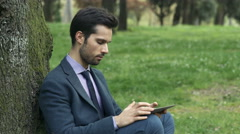 handsome business man working with tablet in a city park - stock footage