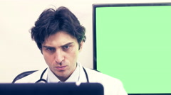 Tired doctor working on computer in medicine office.Green screen - stock footage