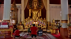 People praying to Buddha Phra Chao Thong Tip in Wat Phra Singh temple, Chiang Stock Footage