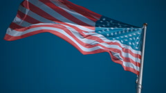 American flag on the flagpole waving in the wind against a blue sky. Slow mo Stock Footage