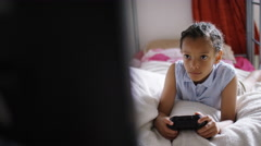 4K Camera reveals young child playing video games, in slow motion Stock Footage