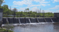Streams of water on the river dam fall down and form waves, splashes and swirls Stock Footage