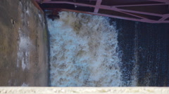 Streams of water on the river dam splashing out from under the gate Stock Footage