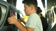 Child  playing video game on the bus - stock footage