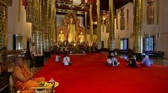 Chiang Mai, Thailand. Circa. Young monk and people praying in Wat Stock Footage