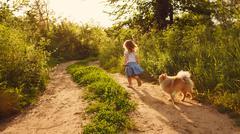 Little girl walking and Spitz Stock Photos