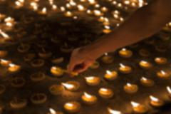 People light candle to pay respect to buddha relic - blur image - stock photo