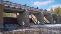 Streams of water on the river dam splashing out from under the gate - stock footage