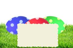 Colorful Painted Easter Eggs in green grass and card isolated on white Stock Photos