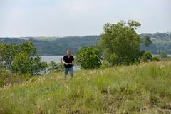 Mature man is walking on the wild grass of riverbank. Stock Photos