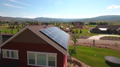 Aerial shot suns reflection on solar panels on roof Stock Footage