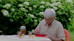 Senior man using digital tablet in summer garden table with tea - stock footage