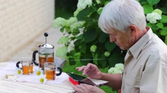 Elderly man using digital tablet in summer garden table with tea - stock footage