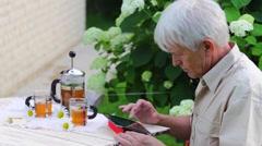 Elderly man using digital tablet in summer garden table with tea Stock Footage