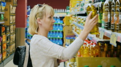 Young woman looking at a bottle of olive or other oil in the supermarket Stock Footage