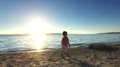 Toddler is playing on the beach - stock footage