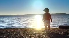 Baby is looking at the sunset. Stock Footage