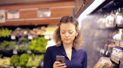 Young woman checking her grocery list on smart phone. Stock Footage