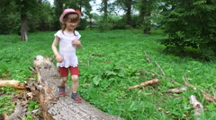 Girl child goes on the trunk of a large tree. Stock Footage