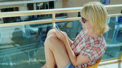 Young woman sitting on the balcony, using a mobile phone. Is typing text looks - stock footage