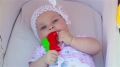 baby lying in her stroller and playing with toy - stock footage