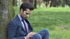 Charming elegant man sit under the tree checking email on his tablet Stock Footage
