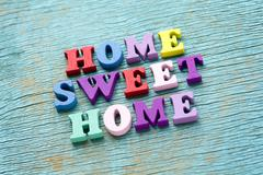 Home sweet home phrase on vintage wooden background Stock Photos