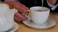 Male hands close up pour tea into a cup and mixing spoon Stock Footage