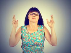 Young woman with glasses crossing her fingers, eyes closed, hoping, asking be Stock Photos