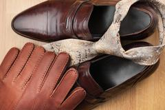 Classic mens brown shoes, tie, gloves, on wooden floor - stock photo