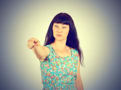 Young woman accusing someone  pointing with finger - stock photo