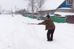 Man cleans snow shovel Stock Photos